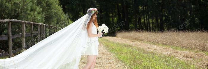 Bride with white veil in the country