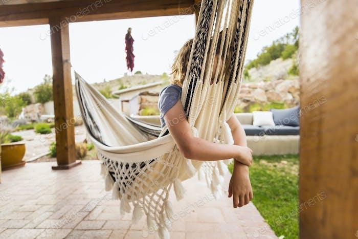 A six year old boy swinging on hammock under patio