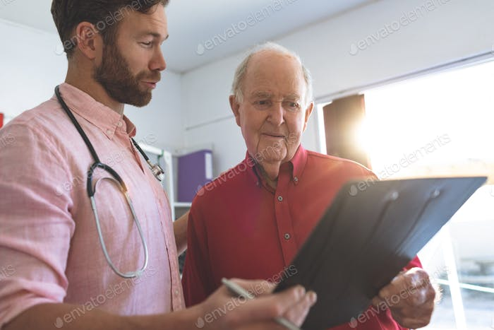 Side view of Caucasian male doctor showing medical report to a Caucasian senior patient in clinic