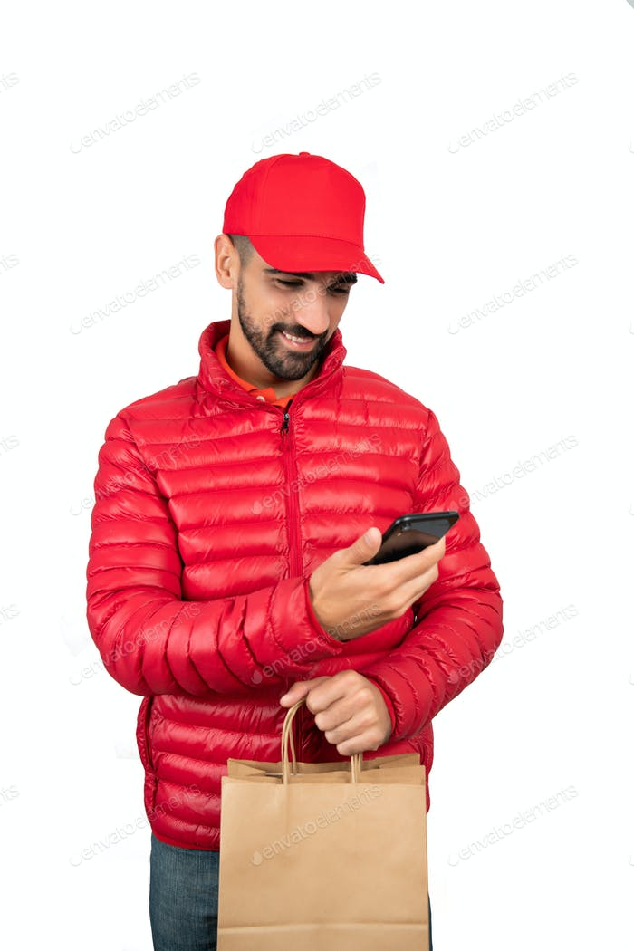 Delivery man holding package and using mobile phone.