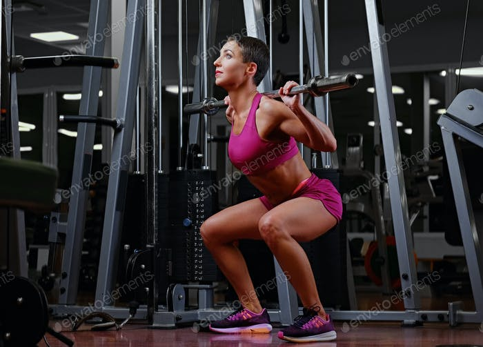 Middle age female with short hair holds the barbell.
