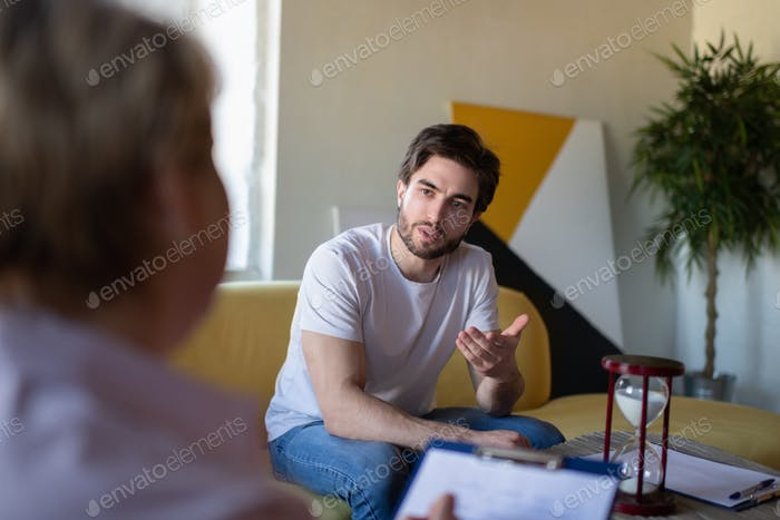 Concerned man sharing thoughts with psychologist
