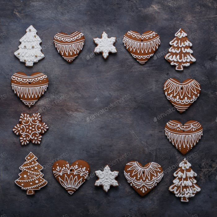 Gingerbread cookies frame on dark background. Snowflake, star, tree, top view copy space