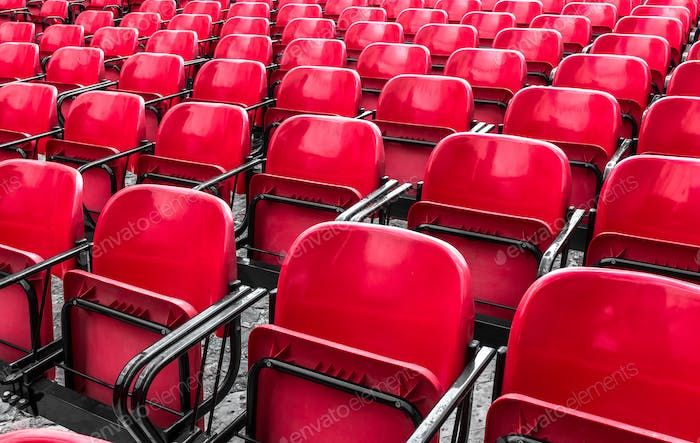 Empty plastic red chairs In outdoor theater
