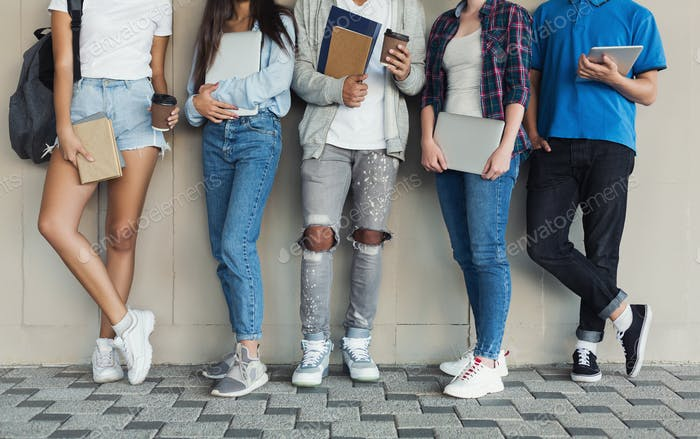 Teenagers standing at campus wall, holding devices and books