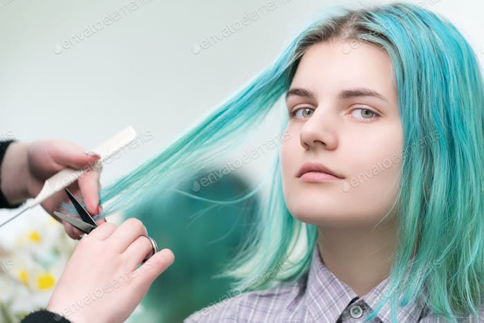 Hairdresser Cutting with Scissors Long Green Hair of Young Woman. Hair Care in Beauty Salon