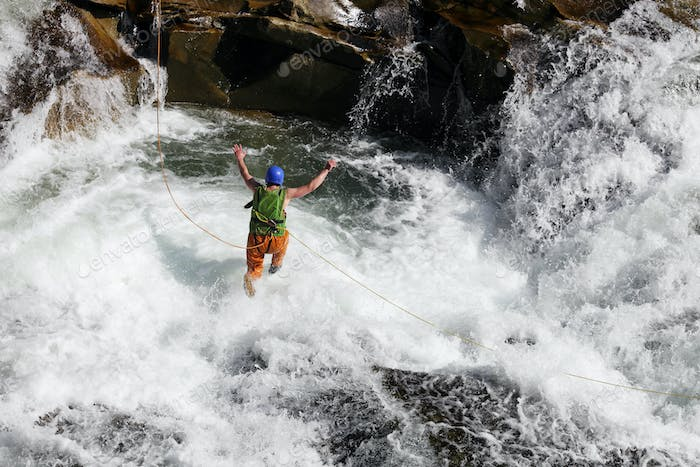 Young man rope jumping in rapid waters of a river