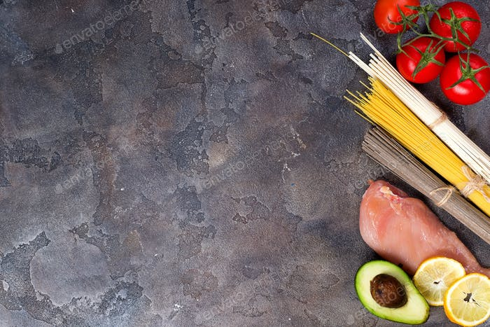 Ingredients for preparing pasta or asian noodle with tomato and meat isolated on stone background.