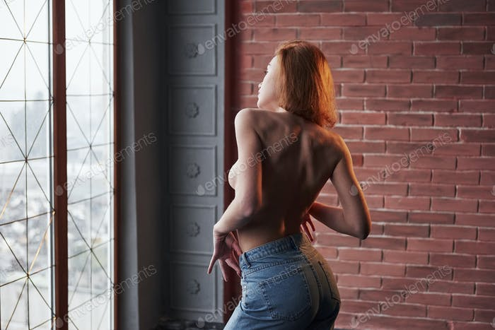 Gentle touching. Hot young blonde with bare chest and jeans stands against the window and brick wall