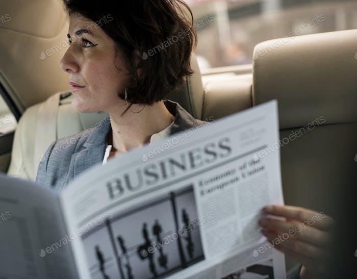 Businesswoman Reading Newspaper Car Inside