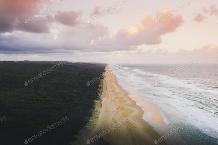 Drone view of coastline under a pastel pink sky