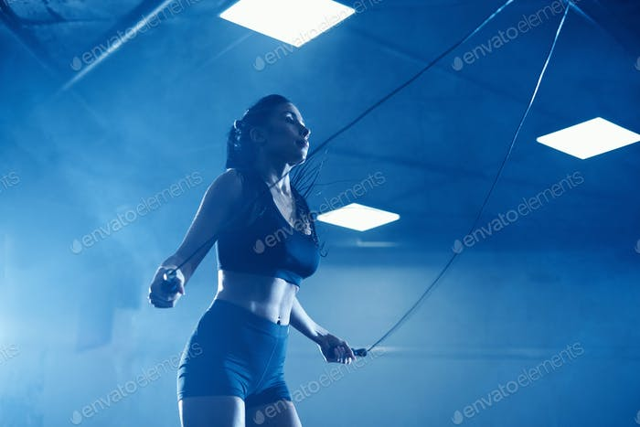 Athletic woman using skipping rope