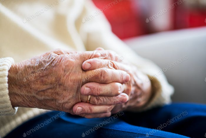 Close-up of a senior woman sitting and praying at home, hands clasped.