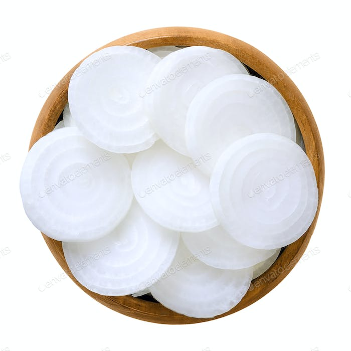 White onion slices in wooden bowl over white
