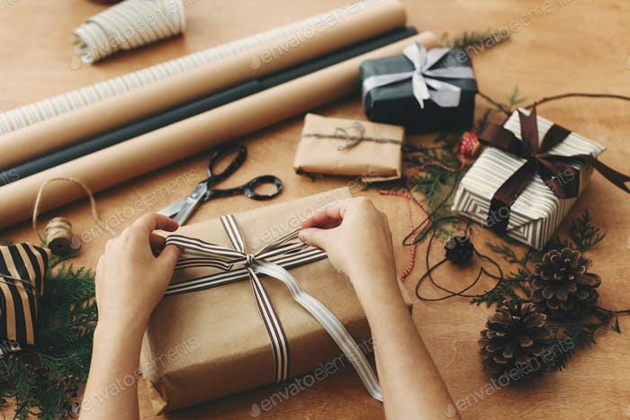 Hands wrapping stylish christmas gift box in craft paper