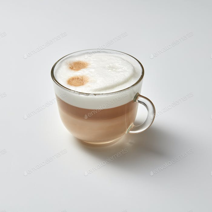 Hot cappuccino in a glass cup with a smile face on a gray background with space for text