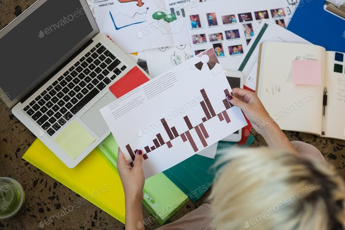 Young Caucasian businesswoman holding graph siting on floor