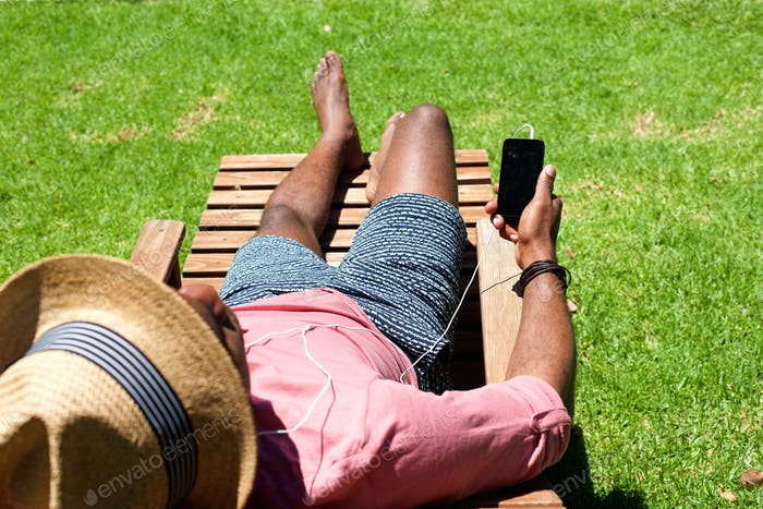 Man lying on lounge chair with a mobile phone