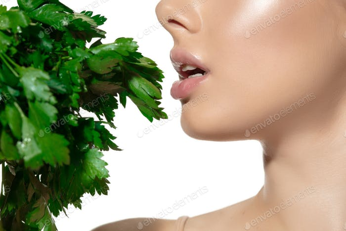 Fresh. Close up of beautiful young woman with green leaves over white background. Cosmetics and