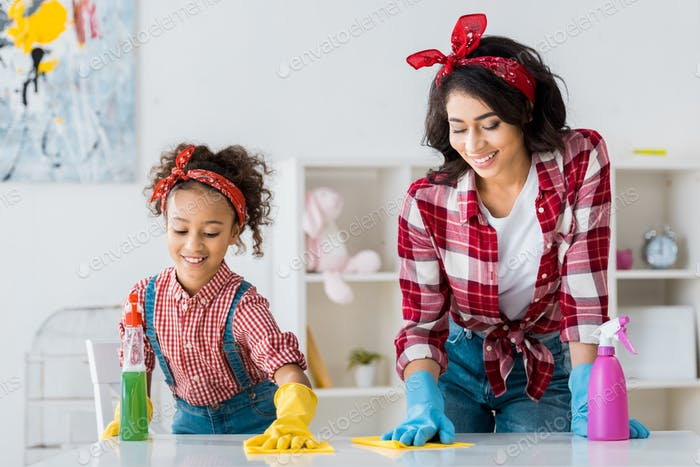 happy african american mom with adorable daughter cleaning table in bright rubber gloves