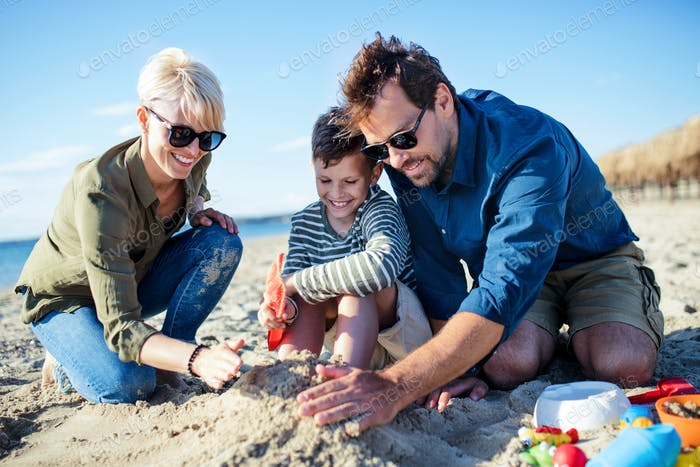 Young family with small boy sitting outdoors on beach, playing