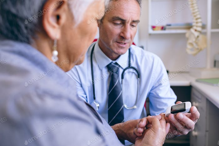 Mature male doctor examining senior woman with glucometer at clinic at retirement home