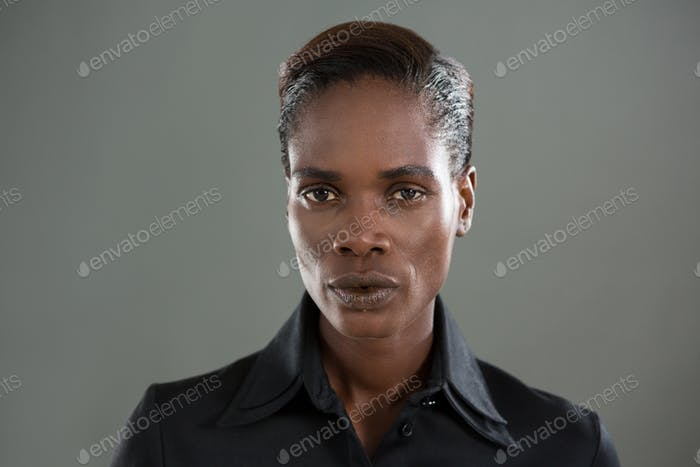 Androgynous man in black shirt posing against grey background