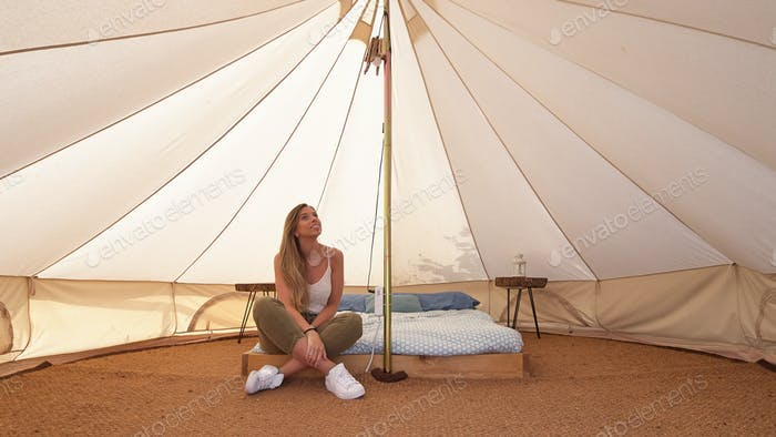 Young woman on the interior of a camping tent