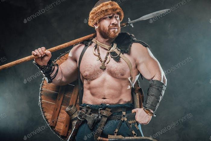 Skandinavischer Krieger mit Speer-Posen vor nebligem Hintergrund