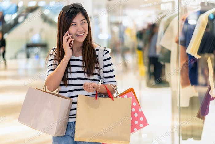 Happy Asian woman calling via the smart mobile phone for checking the product and price