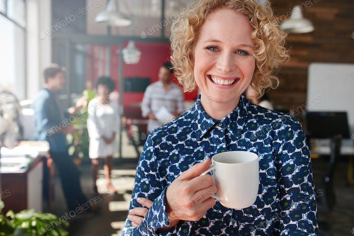 Weibliche kreative professionelle mit einem Kaffee im Büro