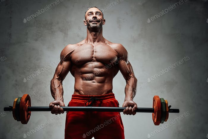Healthy and energetic man doing biceps exercises, focused and looking strong with barbell