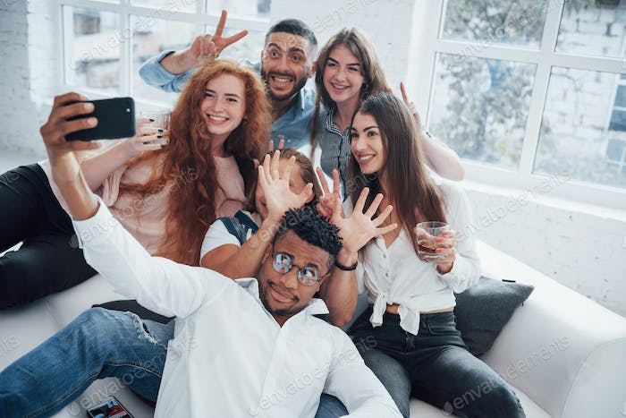 Taking a picture. Cheerful young friends having fun and drinking in the white interior