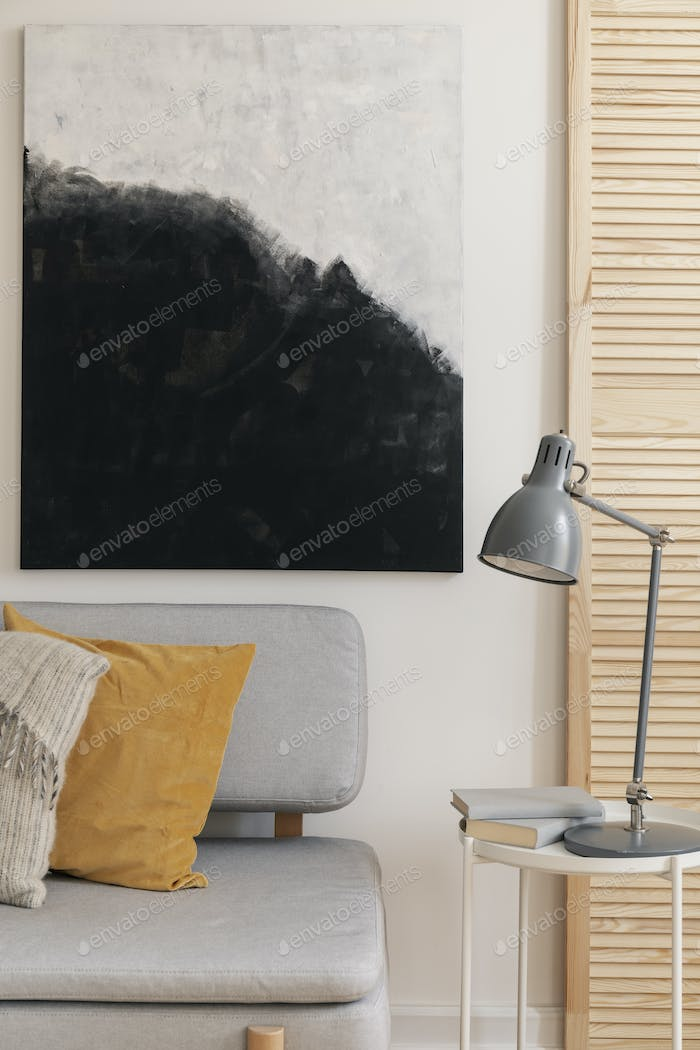 Grey lamp on table next to sofa with pillows in modern living ro