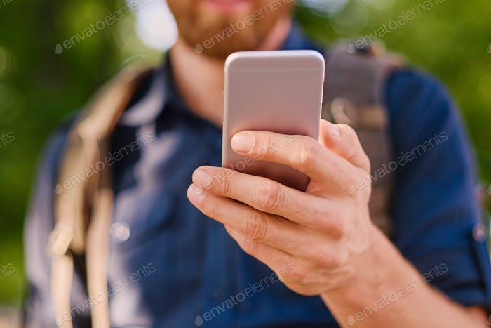 Man holds silver smart phone. Close up.