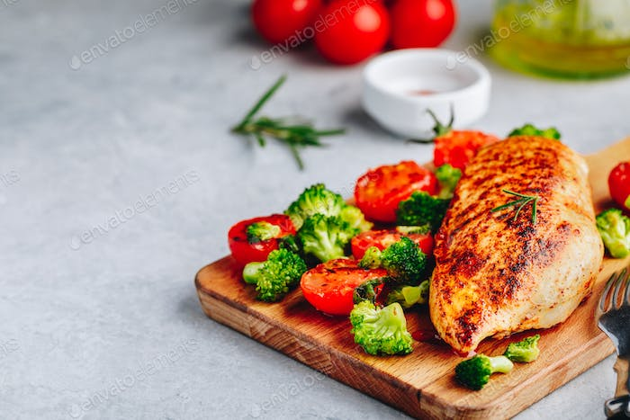 Grilled chicken breast with broccoli and  tomatoes on wooden cutting board