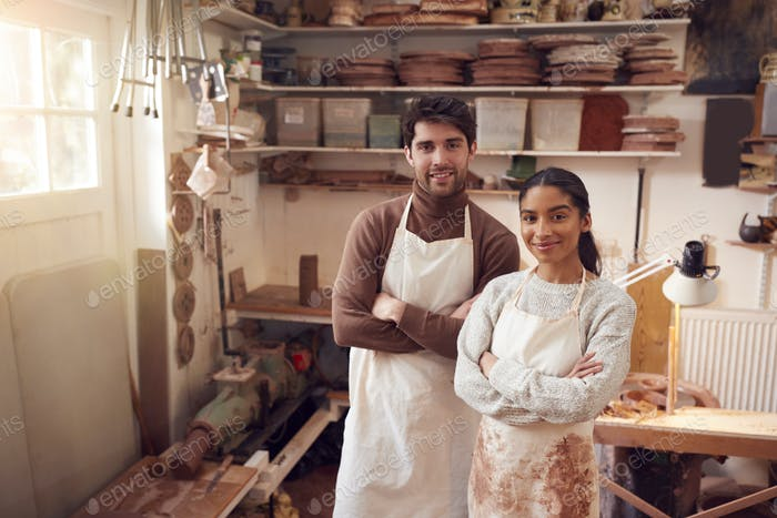 Portrait Of Couple Running Bespoke Pottery Business Working In Ceramics Studio Together