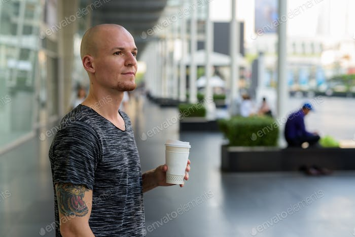 Young handsome bald man thinking while holding paper coffee cup
