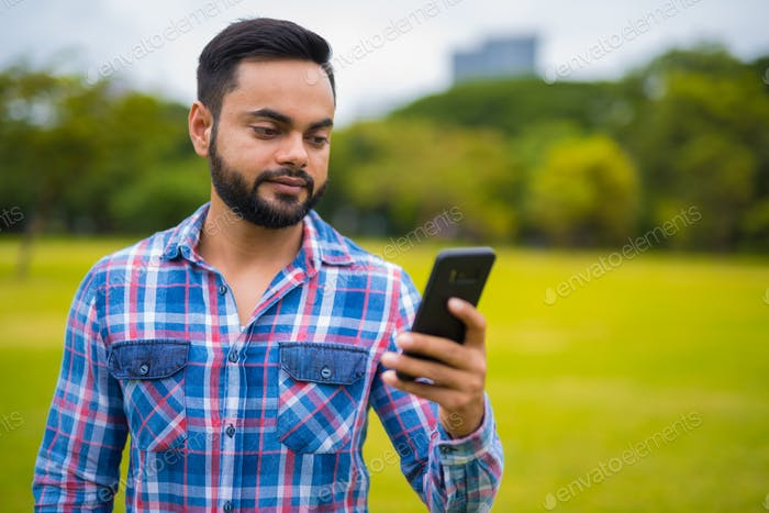 Portrait Of Young Handsome Indian Man In Park Using Mobile Phone