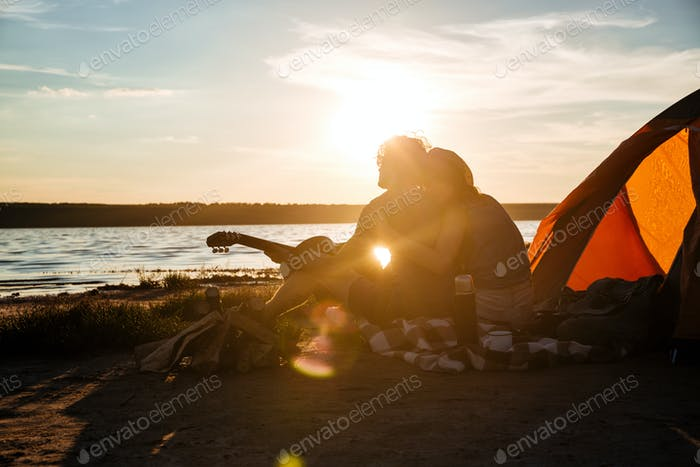 Silhouette of couple sitting near touristic tent and hugging