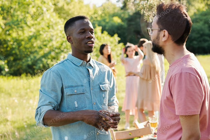 Young African man with glass of wine talking to mixed-race guy outdoors