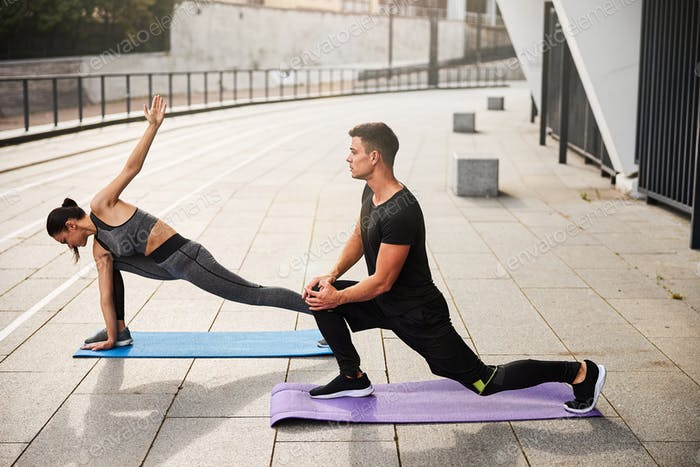 Young athletic couple practicing together outdoors yoga