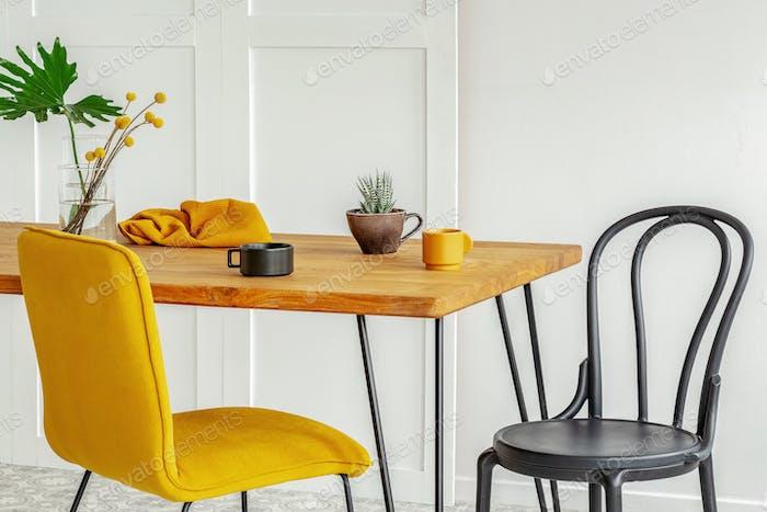 Gelber und schwarzer Stuhl am Holzküchentisch mit Kaffeetassen