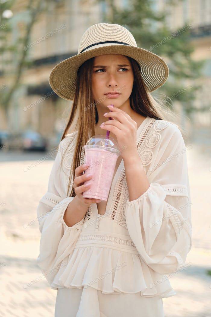 Attractive upset girl in dress and hat holding smoothie sadly looking aside standing on city street