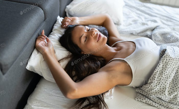 Young beautiful woman sleeping and smiles in her sleep in bed