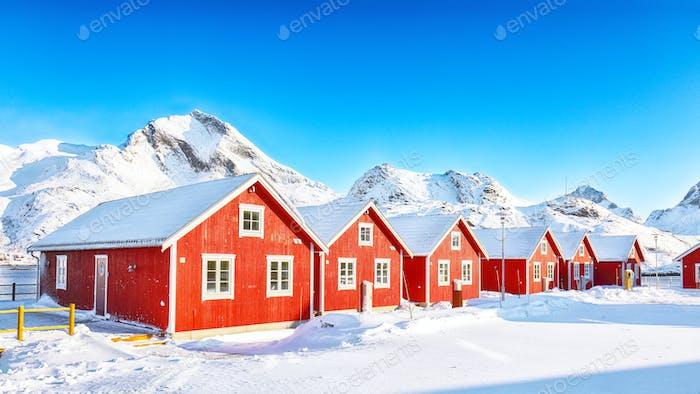 Winterlandschaft mit traditionellen norwegischen roten Holzhäusern am Ufer der Sundstraumen-Straße