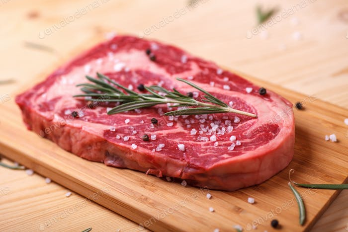 raw uncooked marble beef steak ribeye with rosemary