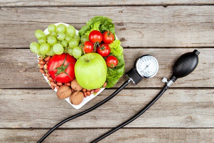 top view of fresh various vegetables, fruits and blood pressure gauge on wooden surface, healthy