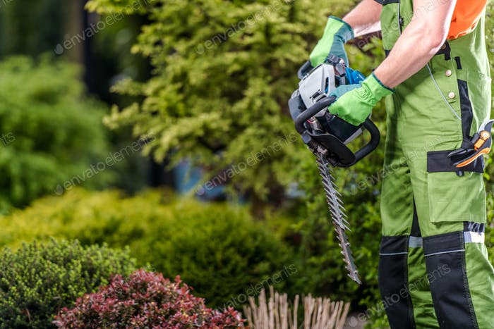 Male Gardener Holding Gasoline Garden Trimmer.