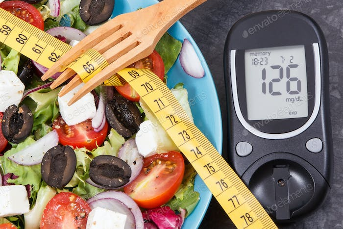 Glucose meter with sugar level, centimeter and greek salad